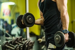 Side view on hands of unknown caucasian man male athlete bodybuilder training at the gym workout using dumbbells biceps curls wearing black shirt standing - weight lifting copy space