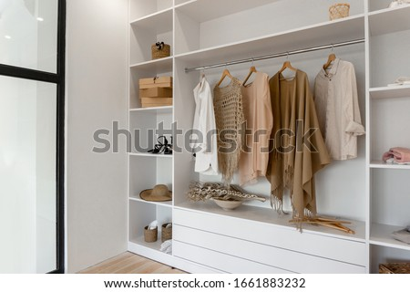 Side view on open space minimalistic scandinavian white wood walk in closet and wardrobe in neutral beige colors Photo stock ©