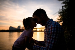 side view on silhouettes of father and little daughter looking at each other against the sunset