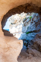 Side view on the round entrance tunnel to unique sea cave in massive rock in Tropea city near the famous Rotonda beach. Tyrrhenian sea shore in Southern Italy in Calabria.