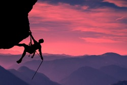 Side view on the young mountainer. Silhouette mountainer in action. The mountainer climbs to a hard route on the rock to reach its goal and success. Landscape of mountains and sunset in the background