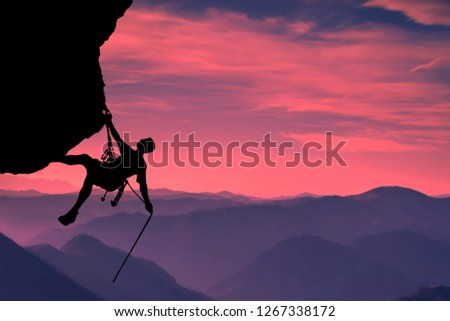 Side view on the young mountainer. Silhouette mountainer in action. The mountainer climbs to a hard route on the rock to reach its goal and success. Landscape of mountains and sunset in the background Stock photo ©
