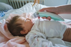 Side view on unknown woman mother using electric baby nasal aspirator mucus nose suction sucking the saliva from baby's nose cleaning while lying on the bed