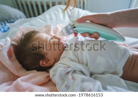 Side view on unknown woman mother using electric baby nasal aspirator mucus nose suction sucking the saliva from baby's nose cleaning while lying on the bed Foto stock ©