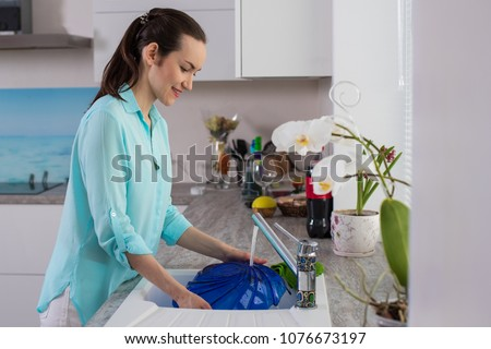 Side view on woman in the turquoise shirt in the interior of the kitchen at the sink washing dish blue in the soft light from the window.