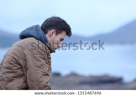 Side view ortrait of a sad man in winter on the beach complaining