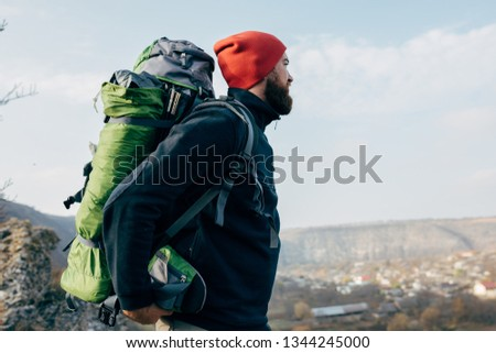 Side view outdoors portrait of young man looking to the horizon in mountains with travel backpack and red hat. Traveler bearded male relaxing after trekking during journey. Travel, lifestyle, sport