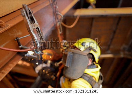 Side view pic of using earth ground connector with unfocused rope access abseiler welder welding safety helmet protective shield equipment while performing difficult task background construction site