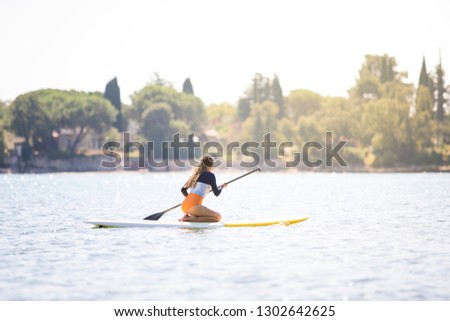 Side view picture of a young sexy woman in swimsuit paddling on her knees on the sup board