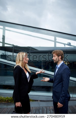 Side view portrait business people discussing work during break, caucasian businesswoman serious speaking to a colleague while they standing outside office, angry boss talk to her employee gesturing