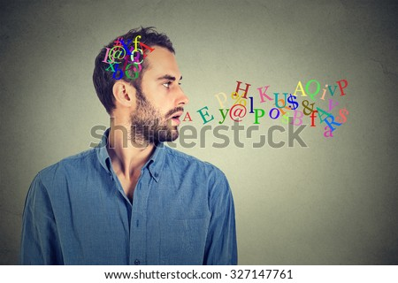 Side view portrait man talking with alphabet letters in his head and coming out of open mouth isolated on gray wall background. Human face expressions, emotions. Communication, intelligence concept