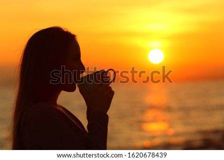 Side view portrait od a woman silhouette drinking coffee at sunrise on the beach