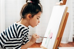 Side view portrait of a concentrated little girl painting with a paintbrush on the paper on an easel at home. A cute child sitting on the floor and drawing in her room during the lockdown.