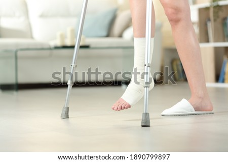 Side view portrait of a disabled woman with bandaged foot walking with crutches at home Photo stock ©