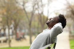 Side view portrait of a happy black man relaxing sitting on a bench in a park