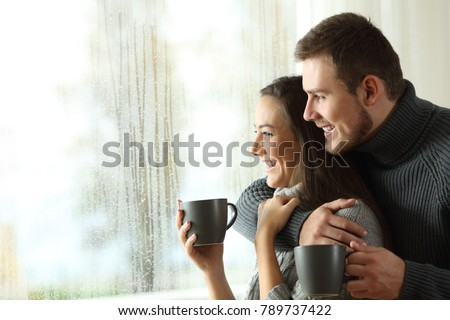 Side view portrait of a happy couple holding coffee mugs looking outside through a window a rainy day of winter at home