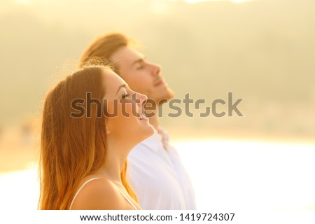 Side view portrait of a happy couple on the beach breathing deep fresh air at sunset
