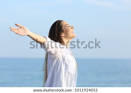 Side view portrait of a happy girl breathing fresh air on the beach outstretching arms #1011924052