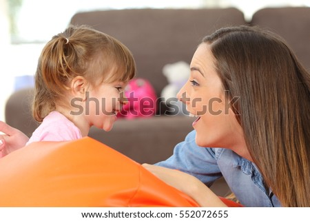 Side view portrait of a happy mother and 2 years baby daughter facing and joking in the living room at home