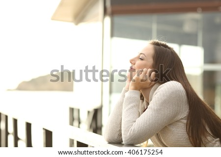 Side view portrait of a happy relaxed woman breathing fresh air outdoor in an hotel or apartment in the beach