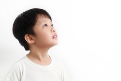 Side view portrait of a little Asian boy looking up against white background.