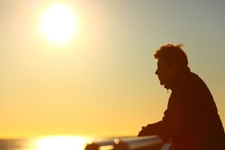 Side view portrait of a man silhouette contemplating sunset on the beach