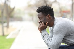 Side view portrait of a pensive serious black man looking away sitting on a park bench