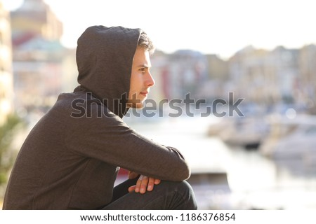 Side view portrait of a pensive teen boy contemplating a port on vacation