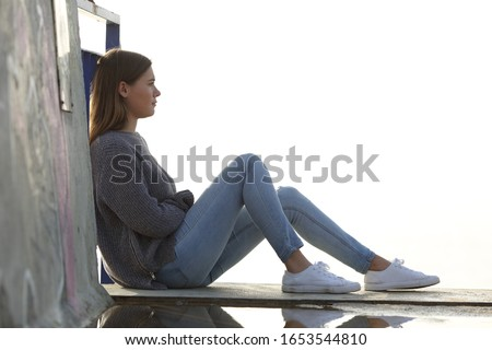 Side view portrait of a pensive teenage girl looking away sitting outdoors