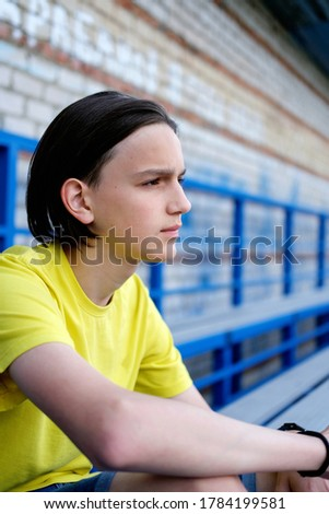 Side view portrait of a pensive thoughtful teen boy. teenager sitting on stadium stairs. thinking of problem or reflecting, anxious melancholic guy serious face feel lonely or doubtful and worried.