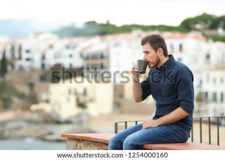 Side view portrait of a relaxed man looking away drinking coffee sitting on a ledge on vacation in a coast town