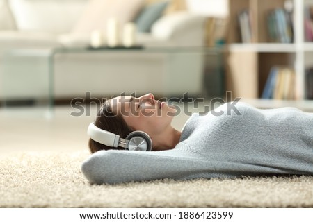 Side view portrait of a relaxed woman listening to music with headphones lying on a carpet at home