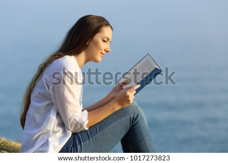 Side view portrait of a relaxed woman reading a book sitting on the beach with the sea in the background