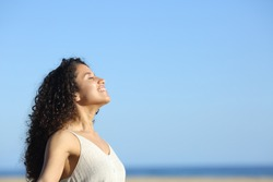 Side view portrait of a relaxed young woman breating and enjoying sun on the beach in summer