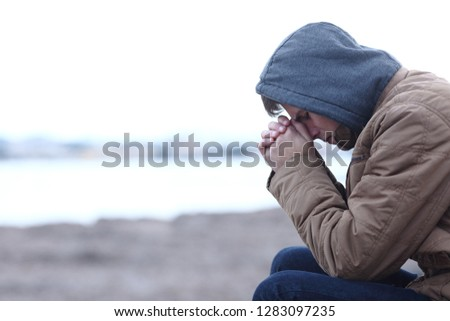 Side view portrait of a sad boy complaining in winter on the beach