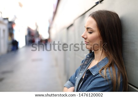 Side view portrait of a sad girl alone complaining leaning on a wall in a solitary street