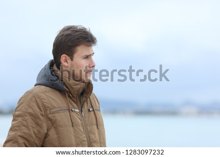 Side view portrait of a sad man looking away on the beach