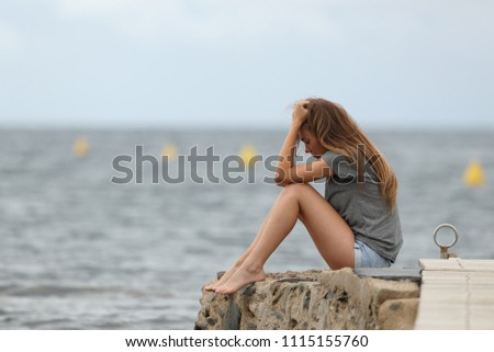 Side view portrait of a sad teen complaining alone with ocean in the background