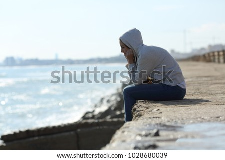 Side view portrait of a sad teenager girl alone on the beach