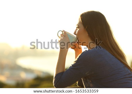 Side view portrait of a satisfied woman drinking coffee at sunset watching views from a balcony
