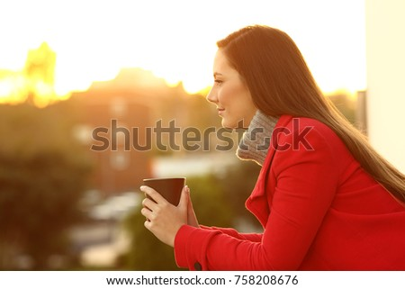 Side view portrait of a serious pensive woman looking away in winter in a house balcony at sunset