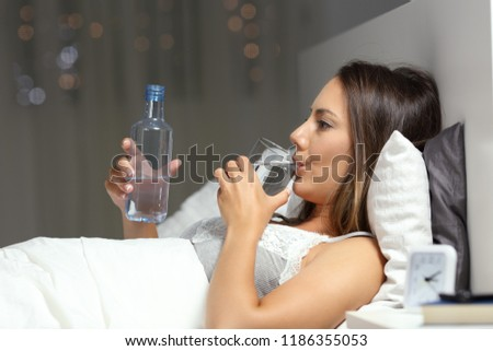 Side view portrait of a serious woman drinking bottled water in the bed in the night
