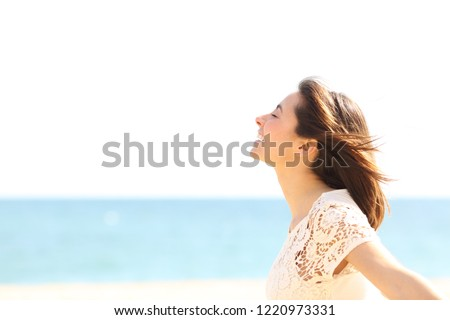 Side view portrait of a smiley lady breathing deep fresh air enjoying the wind on the beach