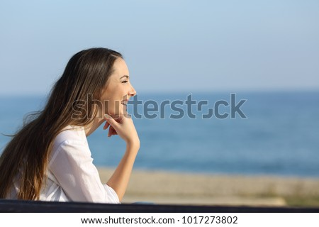 Side view portrait of a smiley woman looking forward on the beach in a sunny day - Shutterstock ID 1017273802
