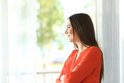 Side view portrait of a thoughtful attractive female looking the green background outside through a window of an hotel room or home