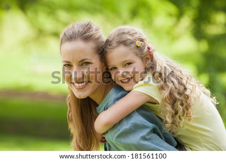 Side view portrait of a woman carrying young girl at the park