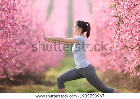 Side view portrait of a woman doing tai chi exercise in a pink flowered field Foto d'archivio ©