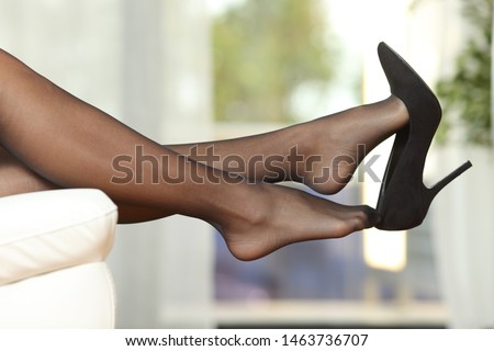 Side view portrait of a woman legs with stockings taking off shoes on a couch at home ストックフォト ©