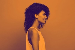 Side view portrait of beautiful attractive African American woman over duotone studio background. Copy Space and duotone.