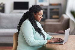 Side view portrait of curvy African American woman using laptop at desk and smiling while enjoying work from home in minimal interior, copy space